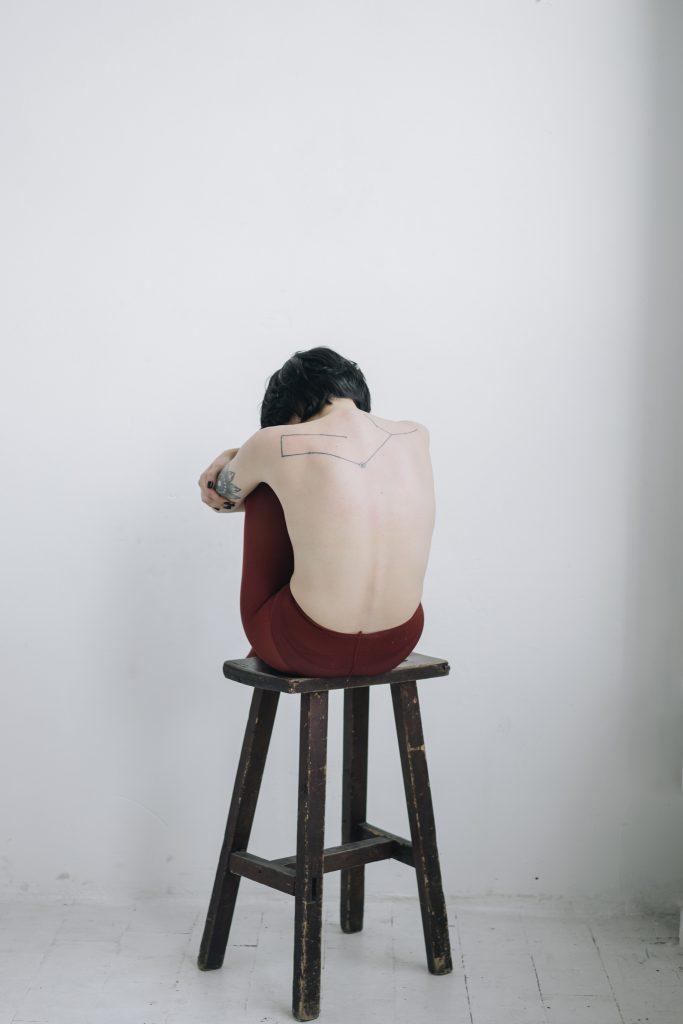Femme-de-dos-assise-sur-une-chaise